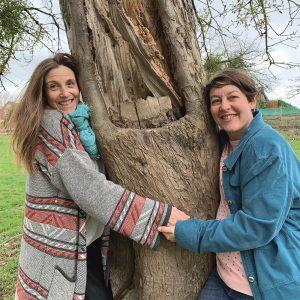 Andrea und Ulla umfassen einen Baumstamm. Andrea Laudenberg aus Bergisch Gladbach – naturzeit: Workshops und Beratung zum Thema Persönlichkeitsentwicklung mit der Kraft der Natur und Heilpflanzen.