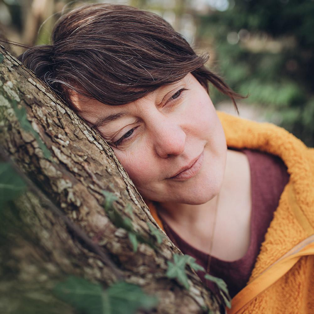 Porträt von Andrea, gegen einen Baumstamm gelehnt. Andrea vermittelt ihr umfangreiches Wissen über die Natur in Form von Workshops und Seminaren, im Raum Köln und Bergisch Gladbach.